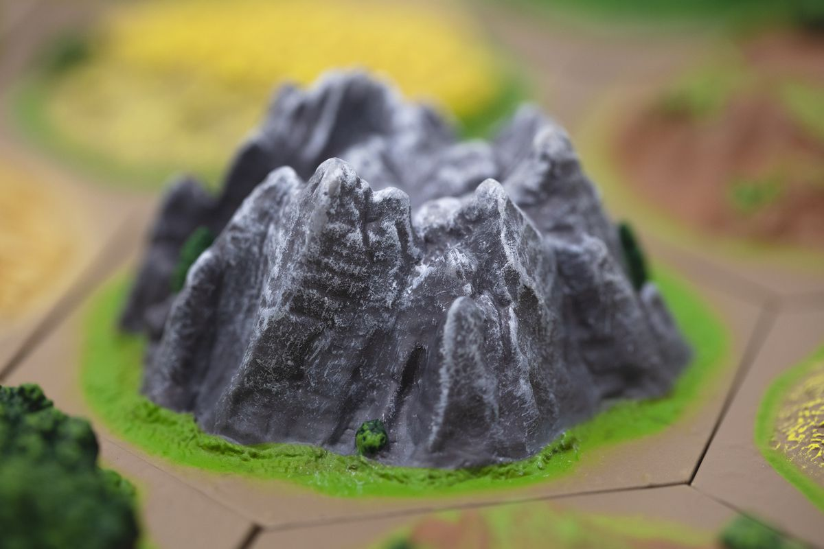 A mountain rising from the table, carefully shaded with light gray and white snow.