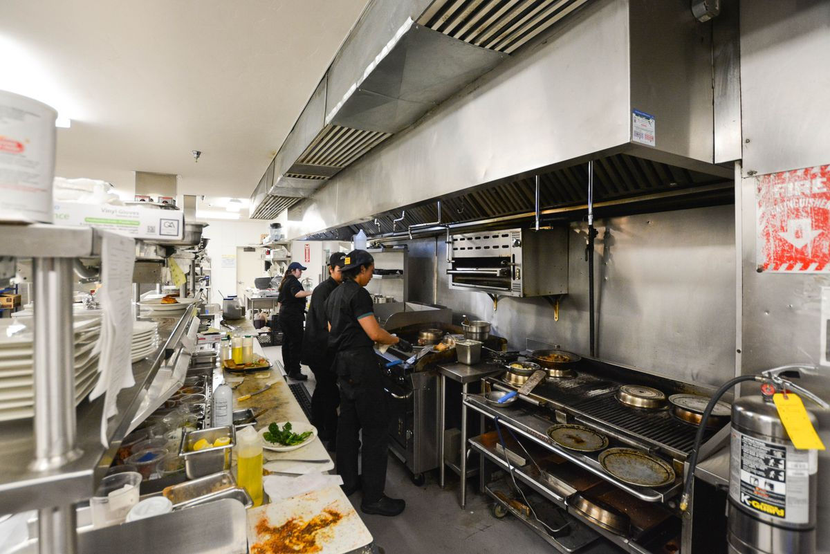 Workers in a bright kitchen preparing meals during a rush.