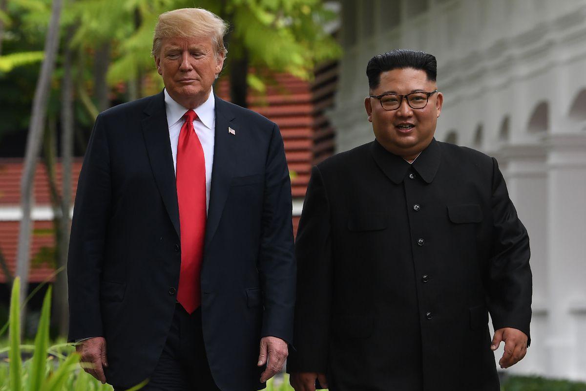 North Korea's leader Kim Jong Un walks with President Donald Trump during a break in talks at their historic US-North Korea summit on June 12, 2018.