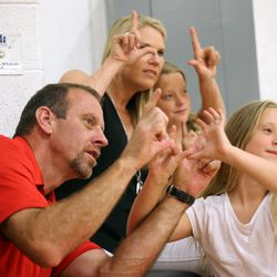 Larry Krystkowiak, head coach for the Utah Runnin' Utes basketball team, makes a U with his daughter Finley while watching his sons play in a Team Camp basketball tournament at the University of Utah in Salt Lake City on Friday, June 12, 2015. His wife Jan and daughter Sam also make U's behind them.