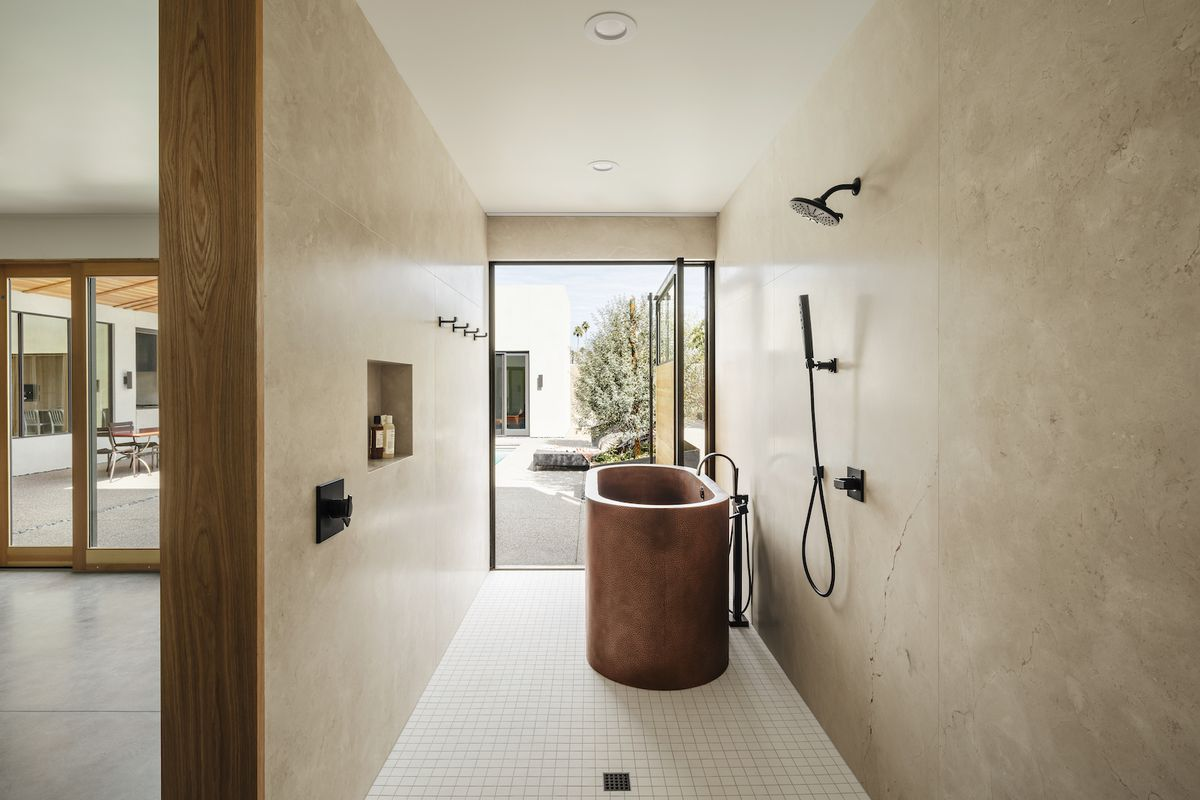 A bathroom with concrete walls, a tub, shower, and an open glass door leading to a courtyard.