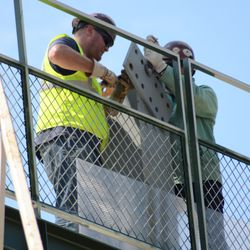 2:20 p.m. Contractors mounting a plate on one of the advertising support mounts, on the right-field porch -