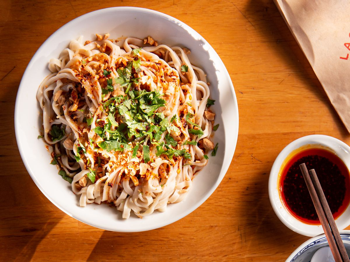 A round plate of thick, cold noodles on a wooden table
