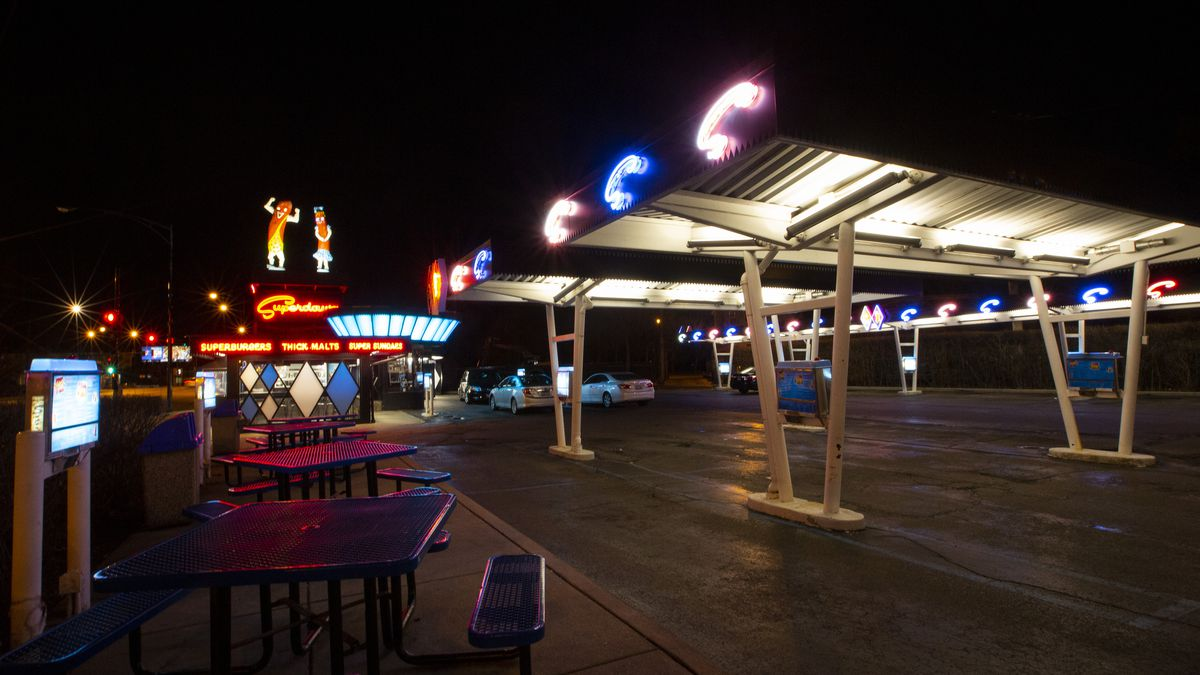 A drive in restaurant's parking lot at night with two giant fiberglass wiener's and plenty of neon.