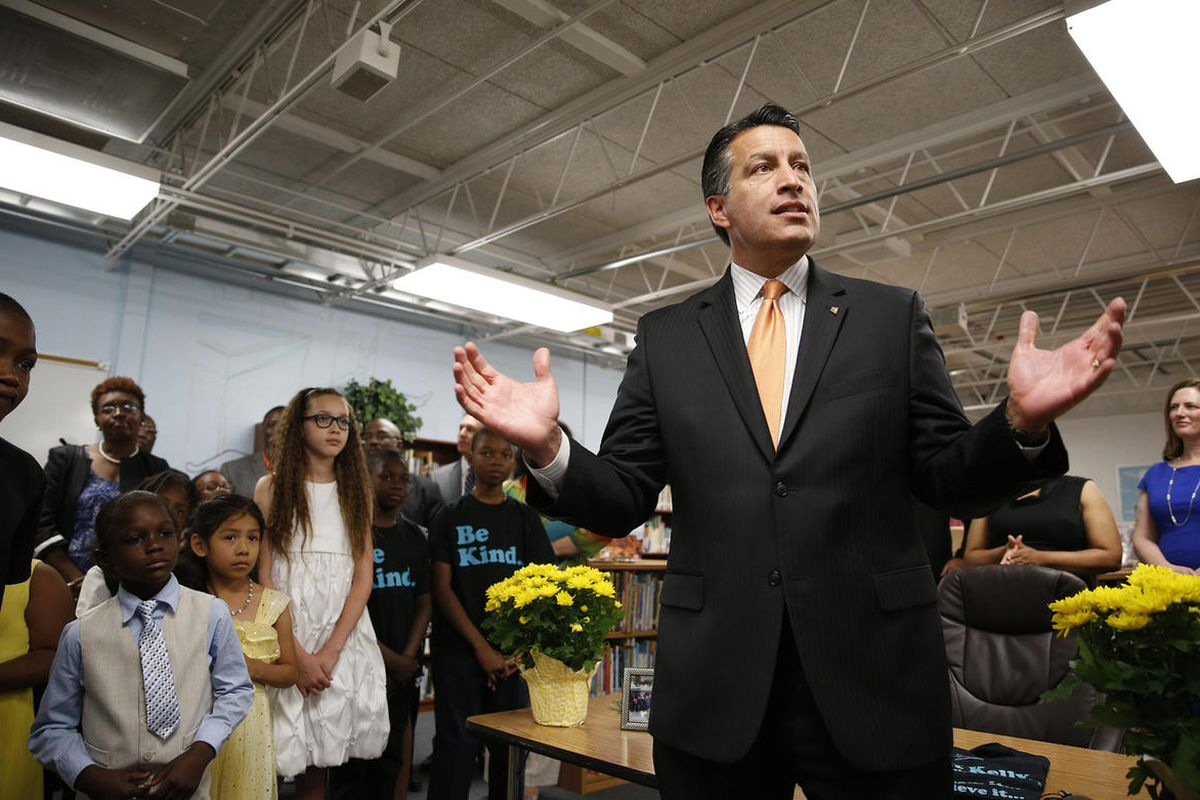 Nevada Governor Brian Sandoval, right, holds a bill signing ceremony Wednesday, June 3, 2015, in Las Vegas. The ceremony was for Senate Bill 432, which allocates millions of dollars for for low performing schools in the 20 poorest zip codes in Nevada. (AP