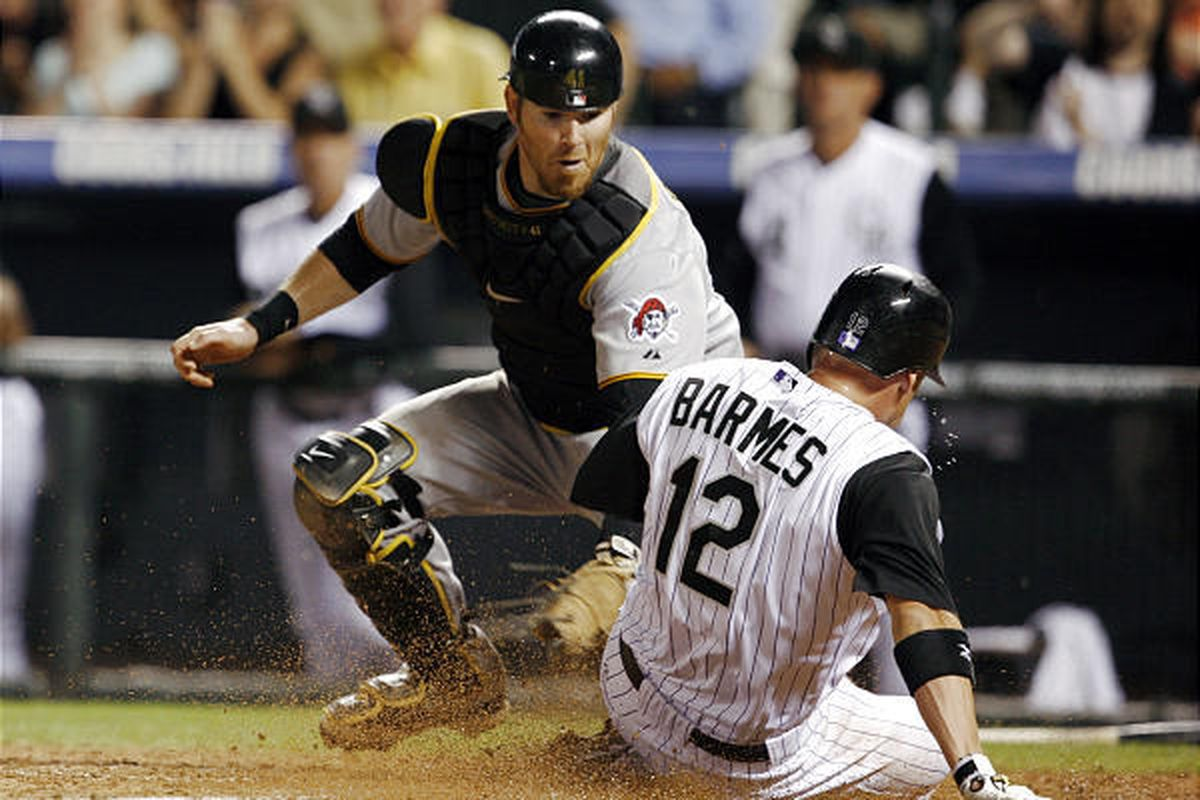 Ryan Doumit, back, turns to apply a late tag as Colorado Rockies' Clint Barmes scores.
