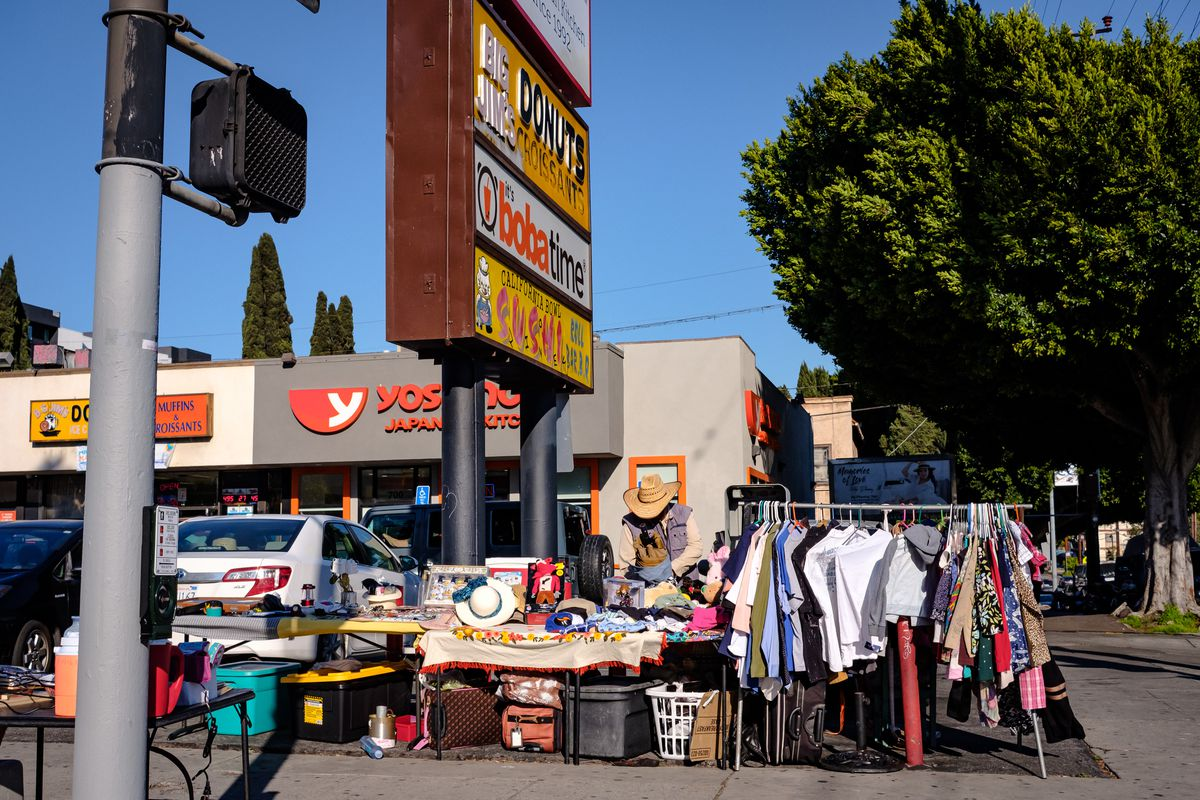 Flea market tables, with a rack of clothes, suitcases, hats and other various items, on the sidewalk outside of a strip mall parking lot.