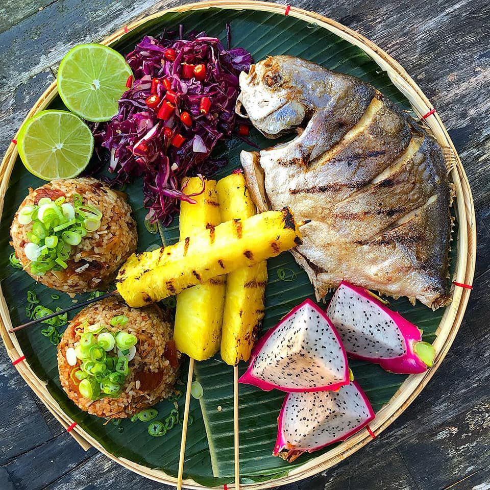 Grilled pineapple, purple cabbage slaw, belly lechon sisig sinangag or garlic fried rice, pompano, and dragonfruit from Kamayan ATL Filipino Pop Up