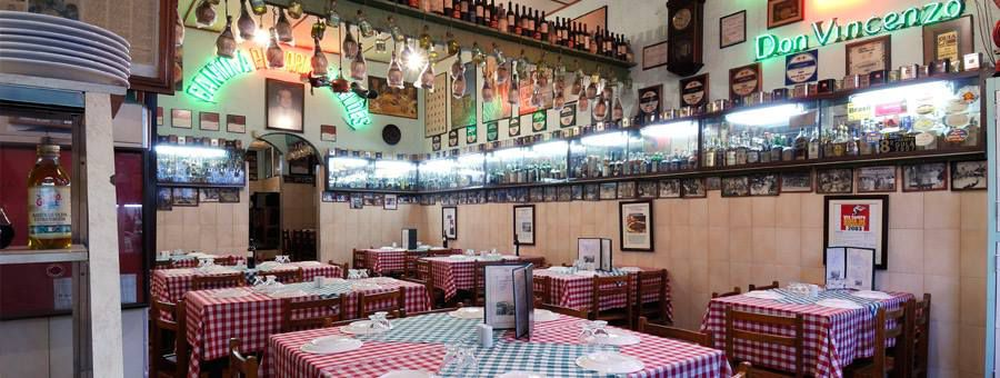 A brightly lit restaurant interior with checked tablecloths on tables, wood panel walls, lots of chachkies, pictures, and bottles for decorations, including some bottles hanging from a crossbeam.