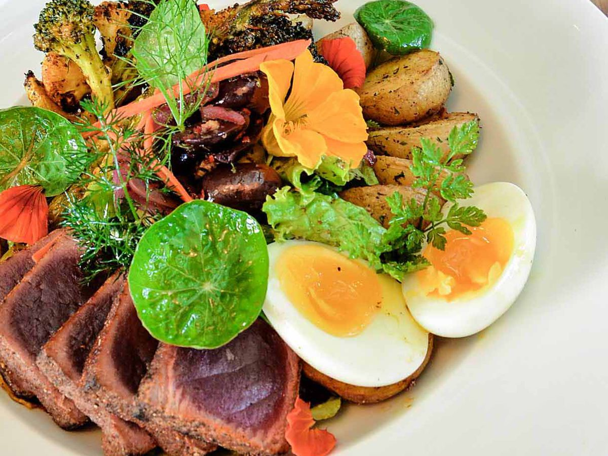A tuna salad with slices of crusted rare tuna, boiled egg, slices potatoes, broccoli, herbs and edible flowers
