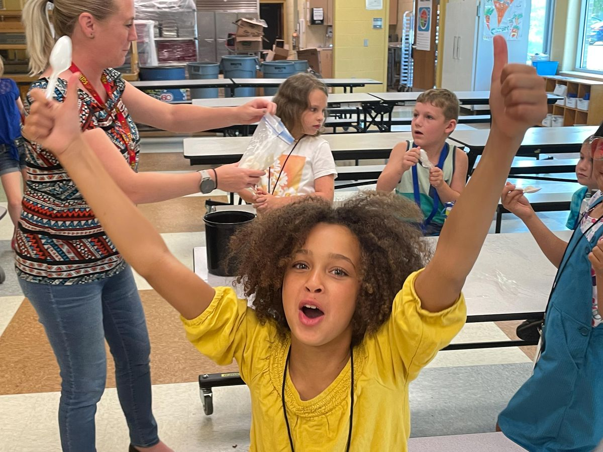 A happy girl, wearing a yellow dress, gives an expressive thumbs up as a teacher and other students have ice cream behind her.