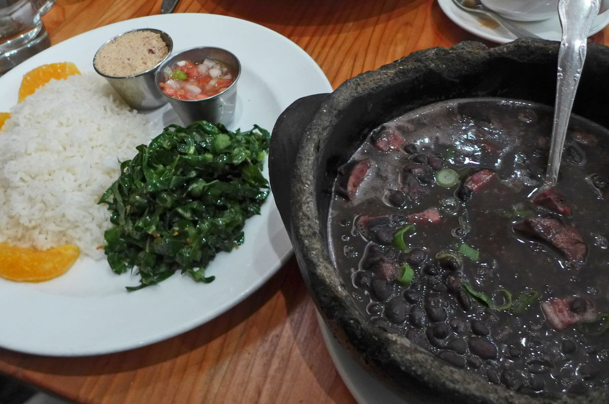 On the right a cast iron pot with pork and black bean stew, on the left a plate of rice, greens, and orange segments.