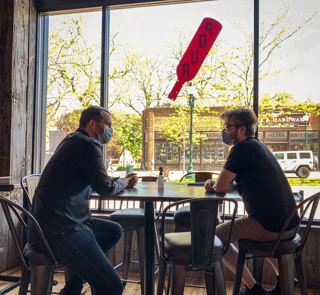 A manager and a chef from Pour Kitchen & Bar sit at a table inside the restaurant wearing masks due to the novel coronavirus.
