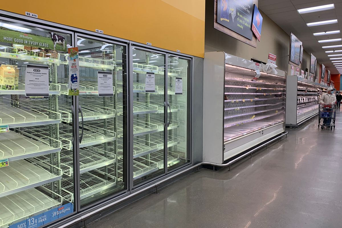 Empty refrigerated shelves in a grocery store.