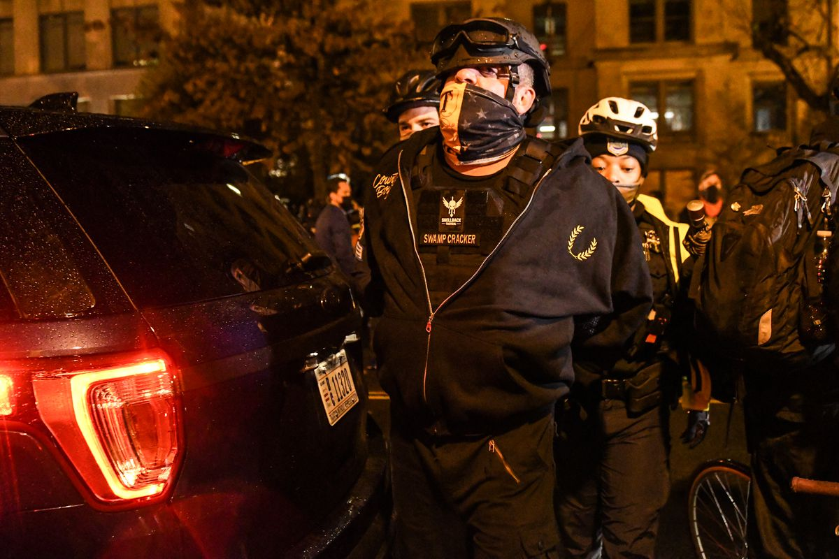 A man in a black hoodie with the yellow laurel arch logo of the Proud Boys and a black helmet is illuminated by streetlights. His hands are behind his back; behind him, is a Black woman in the navy uniform of the DC police.