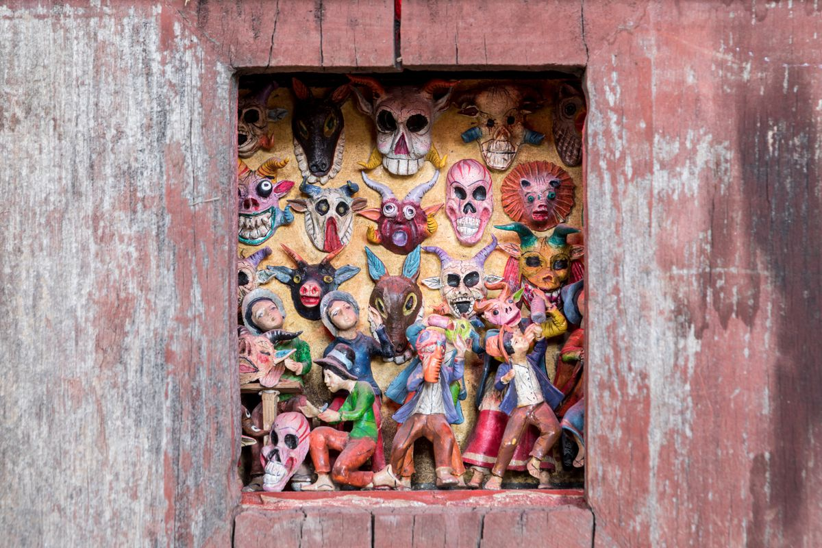 A cut out portion of a red wall contains multiple assorted colorful figurines of people and animals. The wall is decaying.