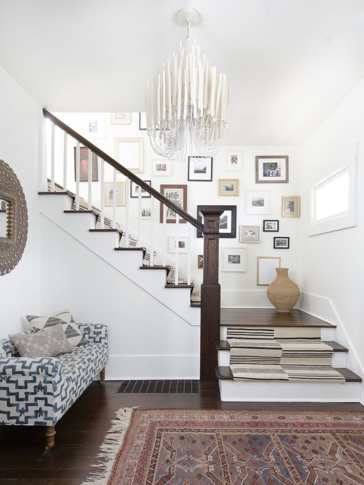 An entry way has a colorful Moroccan rug, a white chandelier with long ceramic tubes, and a striped runner on the stairs.