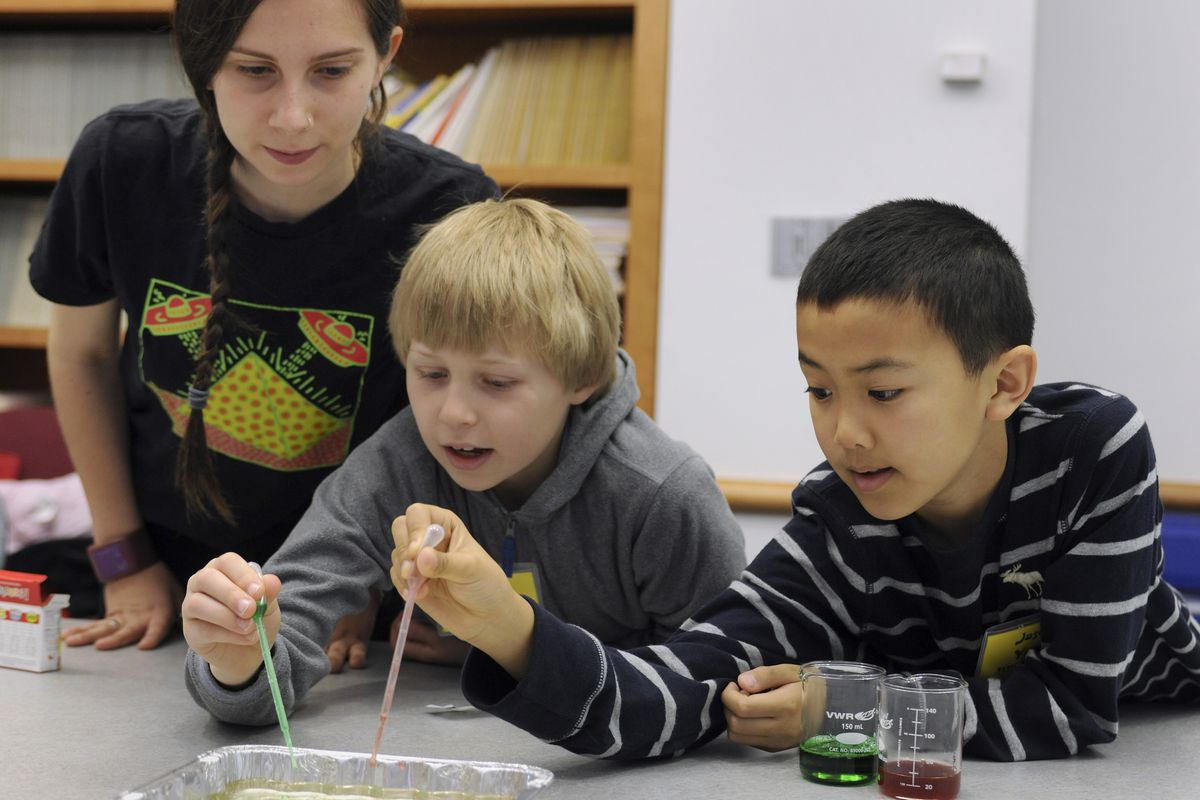"""Graduate student Stephanie Zaleski guides Conlin Audenerd, 8, of Evanston, and Jason Yuan, 10, of Buffalo Grove, as they make """"Edible Slime"""" during one of the workshops that were part of """"Take Our Daughters and Sons to Work Day,"""" at Northwestern University. April 2012"""