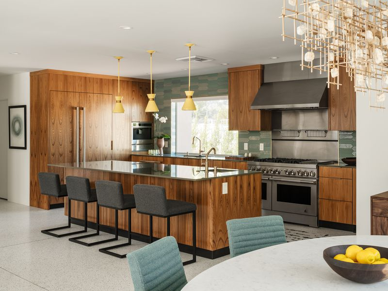A spacious kitchen has teak cabinets, four seats at a large kitchen island, and green accents.