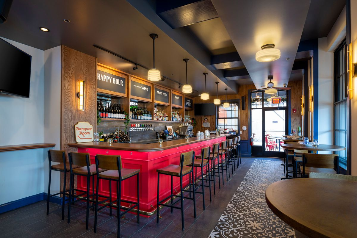 The bar section of Bridget Foy's with red counter stools and a gold tin roof.