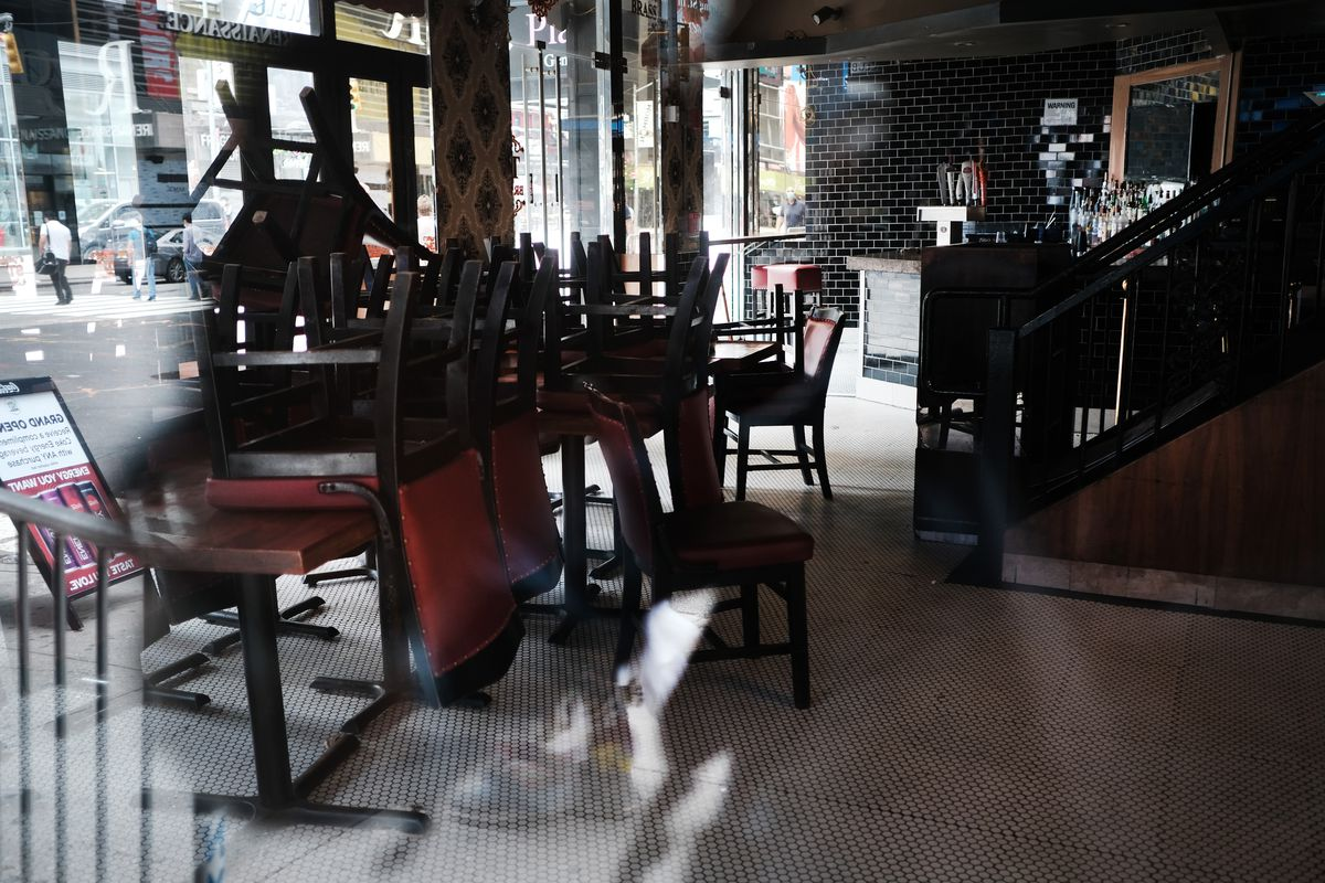 Chairs piled up on indoor tables at a restaurant.