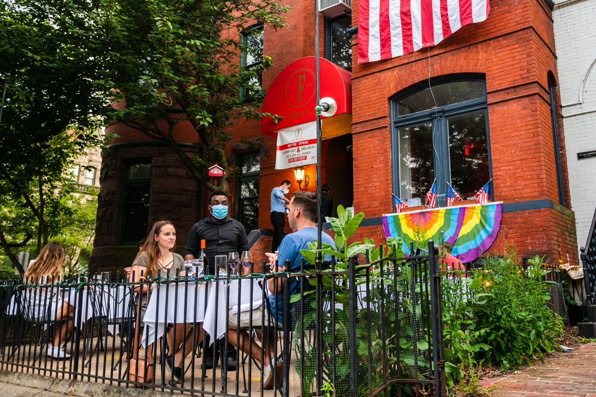 A worker in a blue face mask observes a table for two in front of Italian restaurant Floriana on 17th Street NW