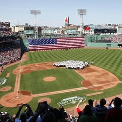 Former Boston Red Sox team member gather on the field while the National Anthem is played during ceremonies to celebrate the 100th anniversary of Fenway Park before a baseball game between the New York Yankees and the Boston Red Sox in Boston, Friday, April 20, 2012.