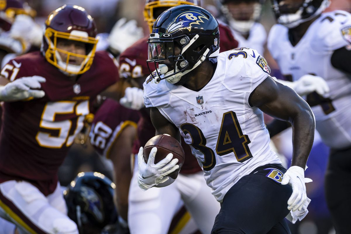 Ty'Son Williams #34 of the Baltimore Ravens carries the ball against the Washington Football Team during the first half of the preseason game at FedExField on August 28, 2021 in Landover, Maryland.