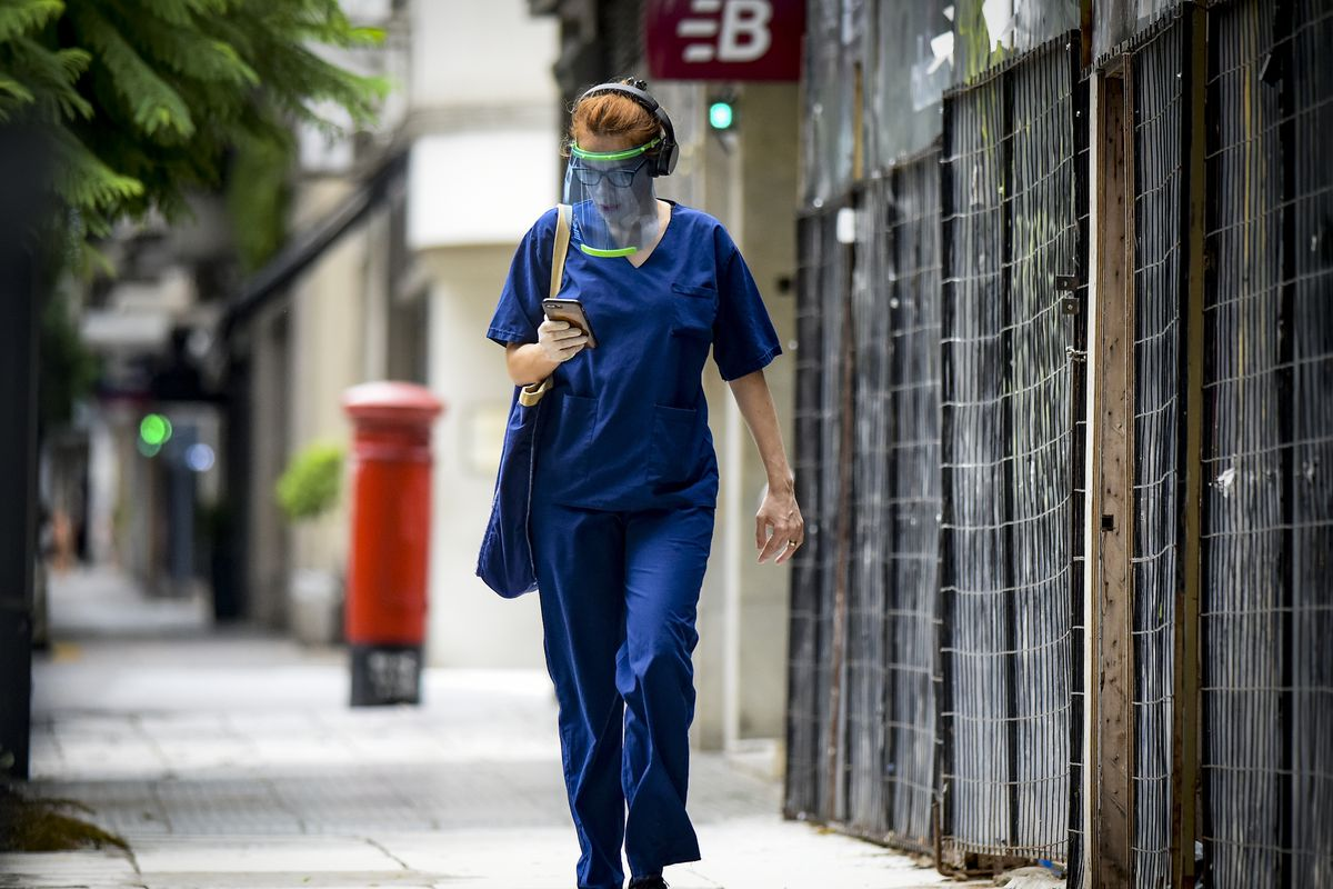 A woman wearing medical gear walks down the street and looks at a phone.