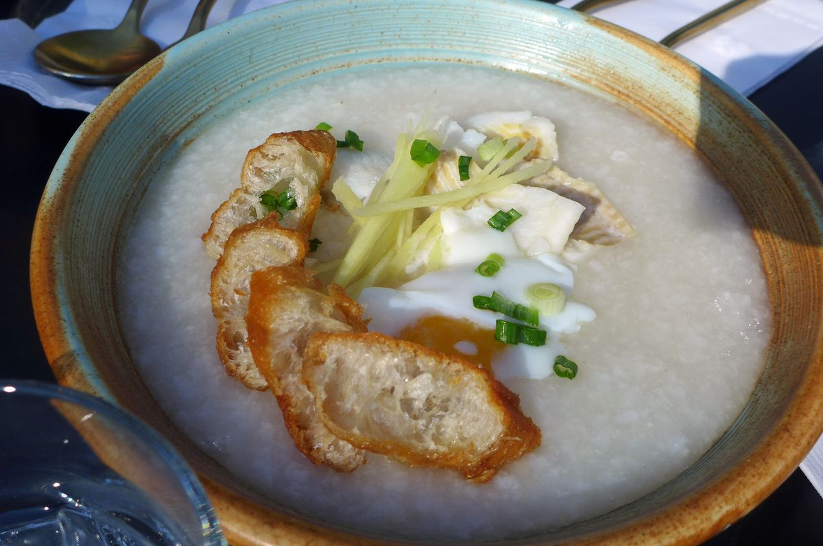 A thick rice soup with fish filet floating on top, along with an egg and slices of fried dough.
