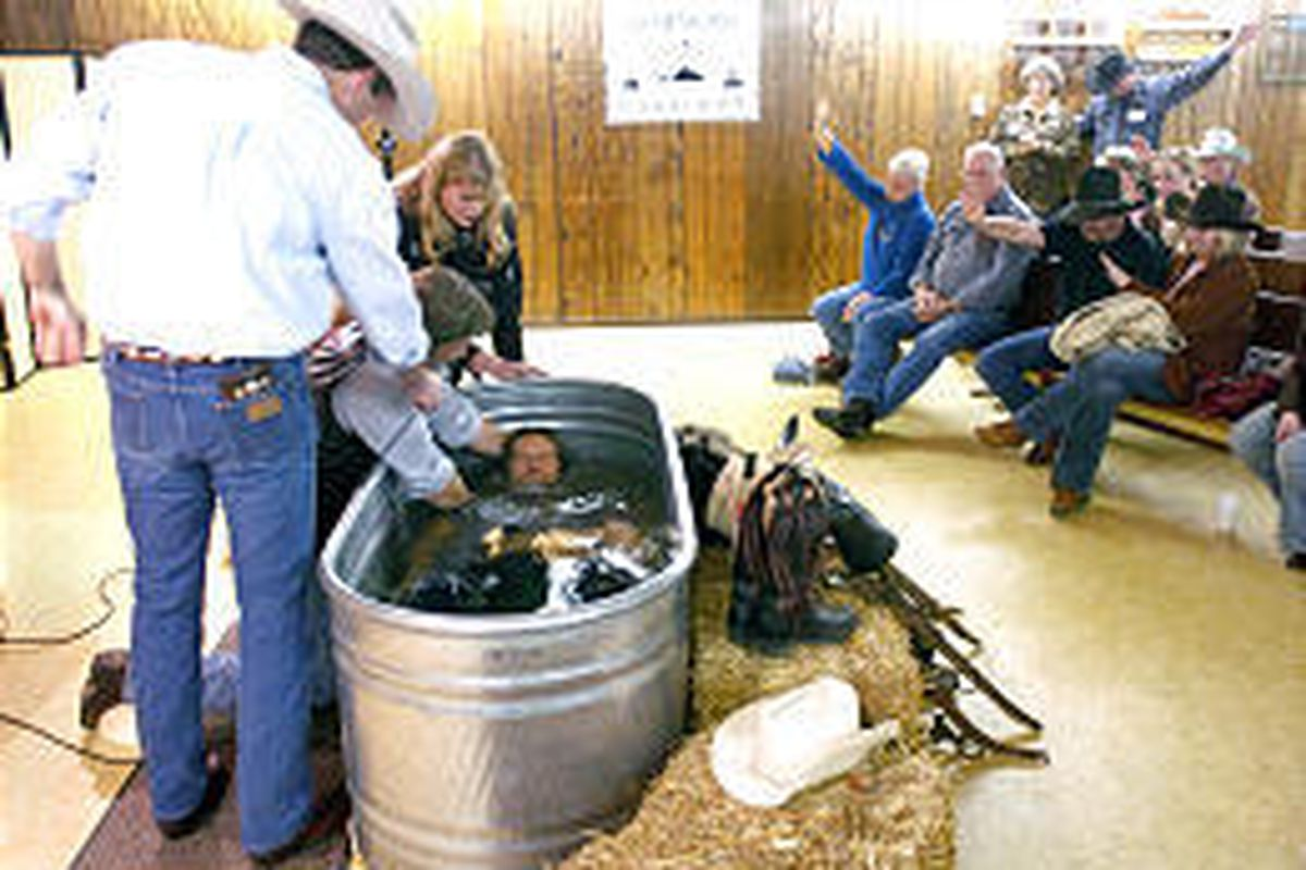 Gene Gordner baptizes Lee Rice in a stock tank at the Flathead Valley Cowboy Church near Kalispell, Mont.