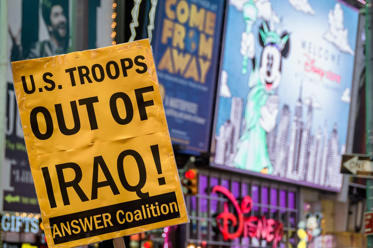 "A protest sign in Times Square reads ""US troops out of Iraq! Answer coalition."""