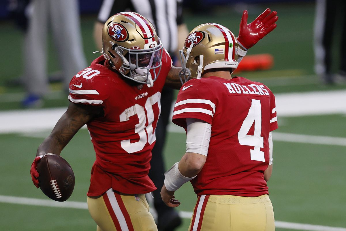 Running back Jeff Wilson #30 of the San Francisco 49ers celebrates a touchdown with quarterback Nick Mullens #4 during the third quarter against the Dallas Cowboys at AT&T Stadium on December 20, 2020 in Arlington, Texas.