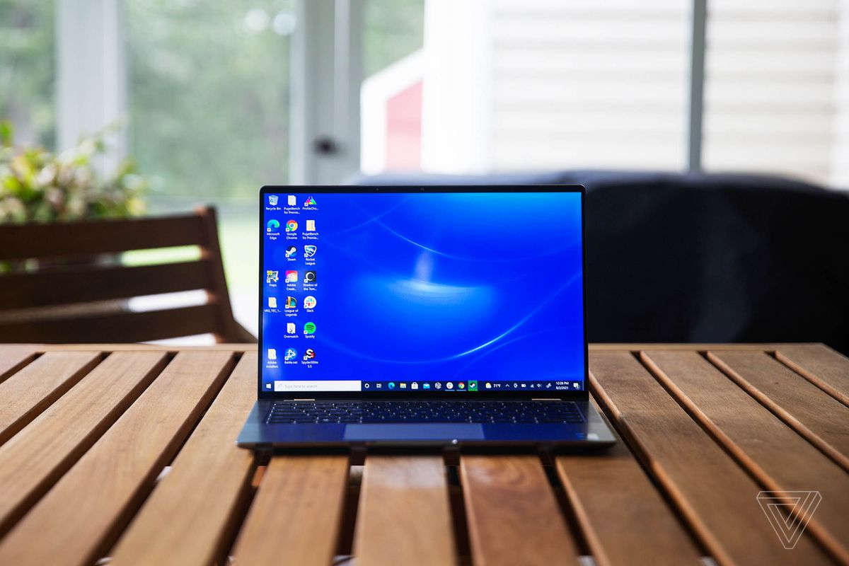 The Dell Latitude 9420 open on a wooden porch table. The screen displays a blue desktop background.