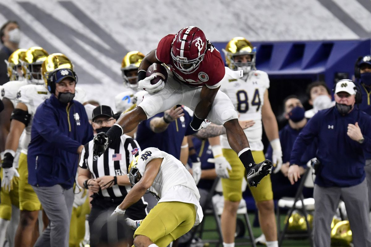 Najee Harris #22 of the Alabama Crimson Tide leaps over Nick McCloud #4 of the Notre Dame Fighting Irish during the College Football Playoff Semifinal at the Rose Bowl football game at AT&T Stadium on January 01, 2021 in Arlington, Texas. The Alabama Crimson Tide defeated the Notre Dame Fighting Irish 31-14.