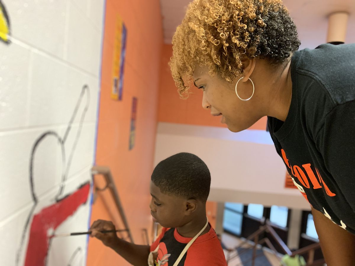 Principal Elizabeth Meyers watches as a student paints a mural.