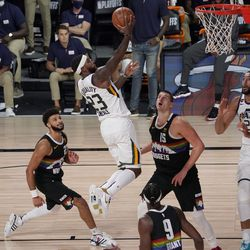 Utah Jazz's Royce O'Neale (23) goes up for a shot between Denver Nuggets' Jamal Murray, left, Jerami Grant (9) and Nikola Jokic, center right, as the Jazz' Rudy Gobert (27) looks on during the second half an NBA first round playoff basketball game, Tuesday, Sept. 1, 2020, in Lake Buena Vista, Fla.