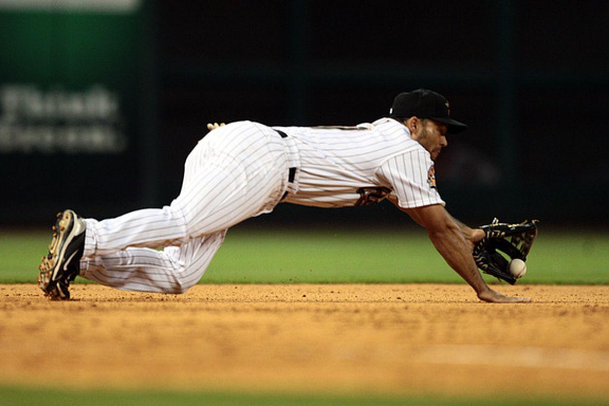 HOUSTON - MAY 03:  Third baseman Pedro Feliz #77 of the Houston Astros knocks down a hard hit ball during a baseball game against the Arizona Diamondbacks at Minute Maid Park on May 3, 2010 in Houston, Texas.  (Photo by Bob Levey/Getty Images)