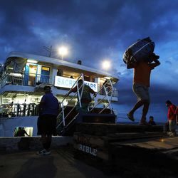People carry belongings after riding a ferry from Cebu City to Leyte Island in the Philippines, Tuesday, Nov. 19, 2013, following Typhoon Haiyan.