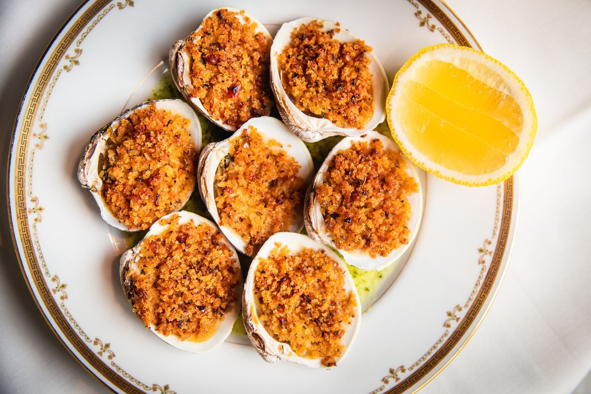 A plate with seven clams filled with bread crumbs, with a lemon half on the side