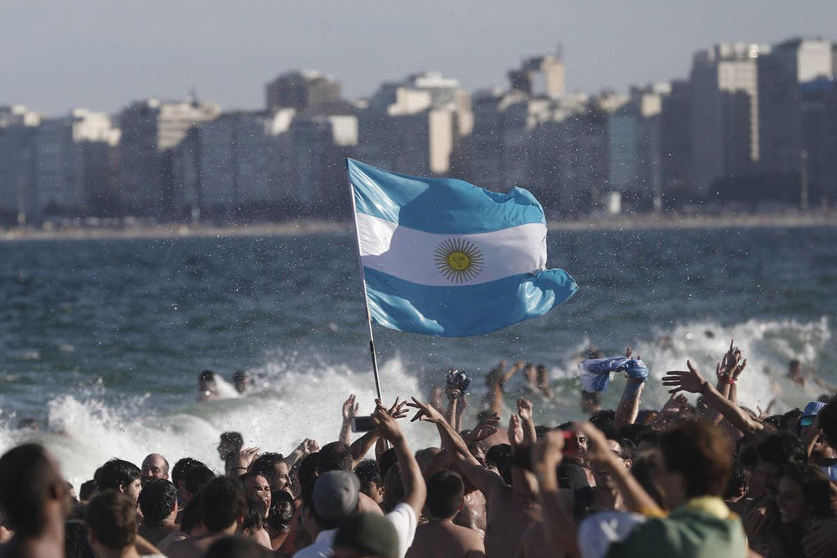 Fans of the Argentina national soccer team wave their country's national flag as they celebrate their team's World Cup quarterfinal 1-0 victory over Belgium, on Copacabana beach, in Rio de Janeiro, Brazil, Saturday, July 5, 2014.