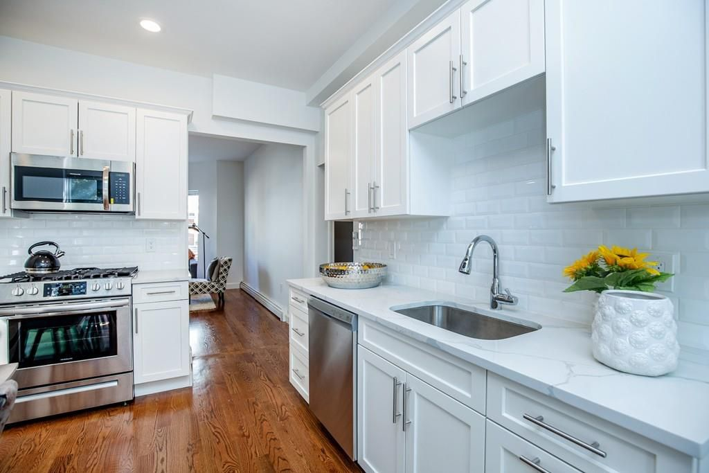 A modern kitchen with a long counter and another shorter counter, with an entryway separating them.