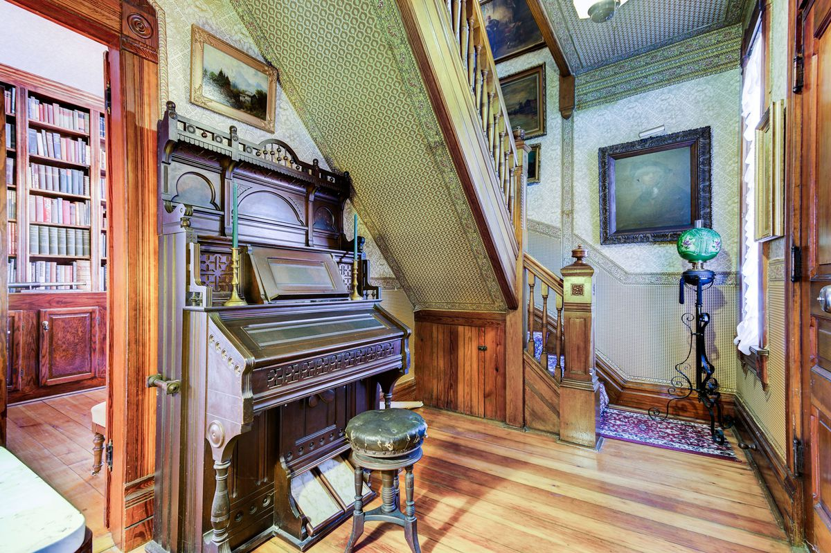 The foyer of a Victorian home features a staircase leading up, wood floors, and a vintage piano.