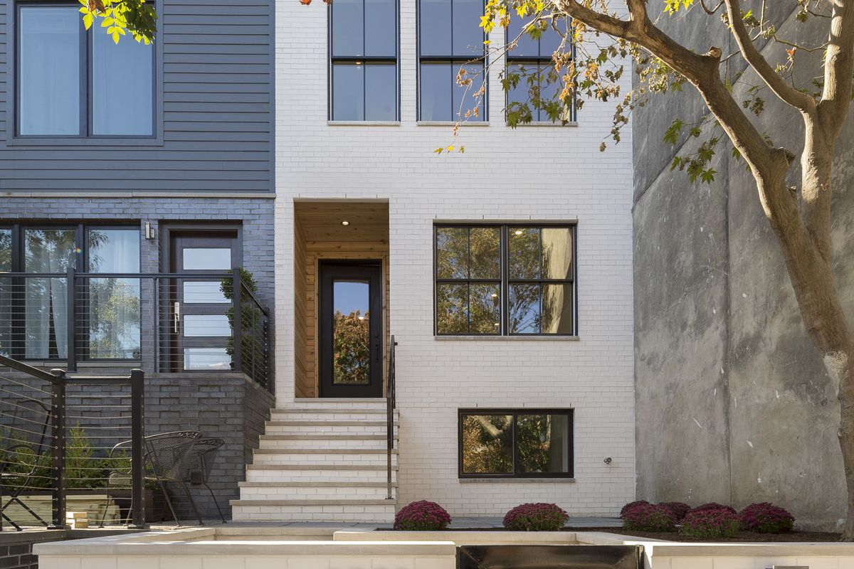 A white brick rowhome in Philadelphia's Fitler square neighborhood with stairs leading up to a custom black door wrapped in cedar.