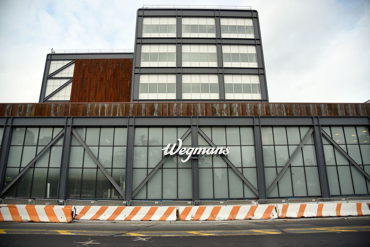 """A building with a glass and steel exterior, with a sign that says """"Wegmans"""" on the front."""