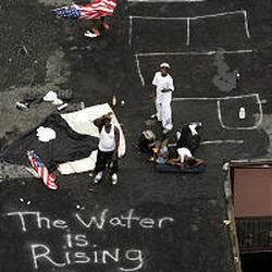 Residents wait on a roof Thursday to be evacuated from the floodwaters of New Orleans after Hurricane Katrina.