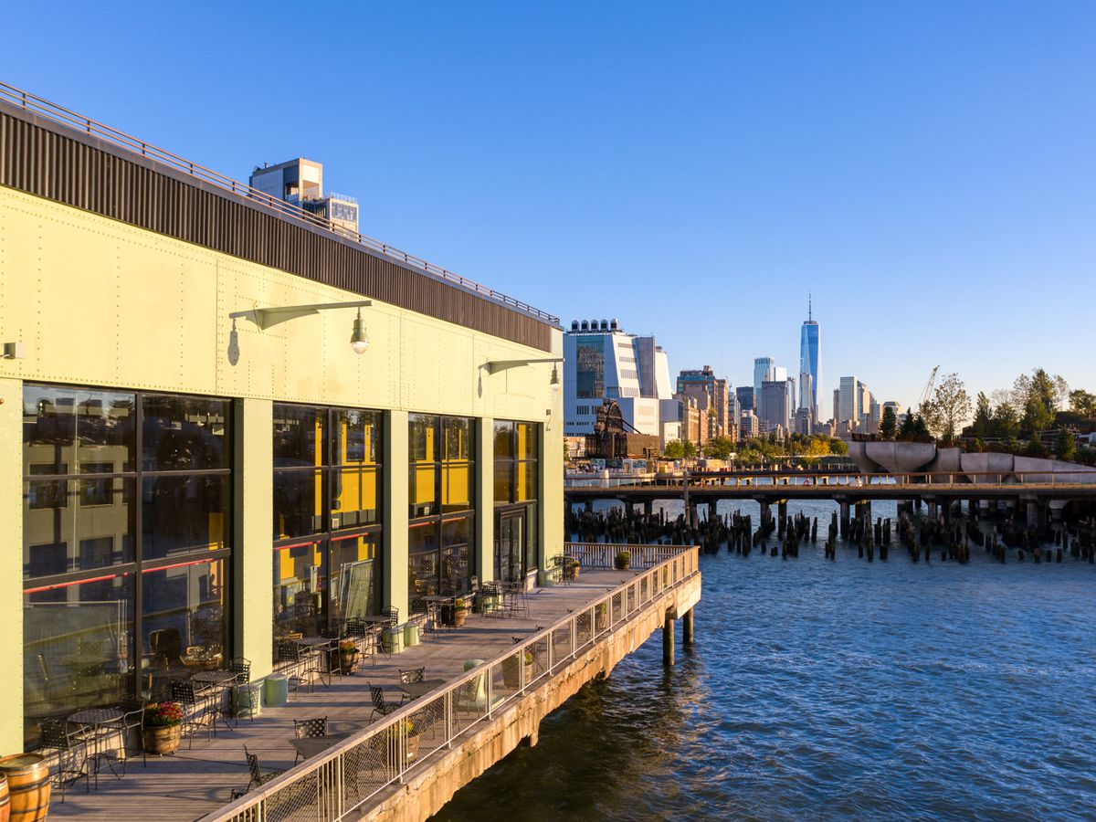 A building on a pier with outdoor dining set up and an NYC building skyline in the background