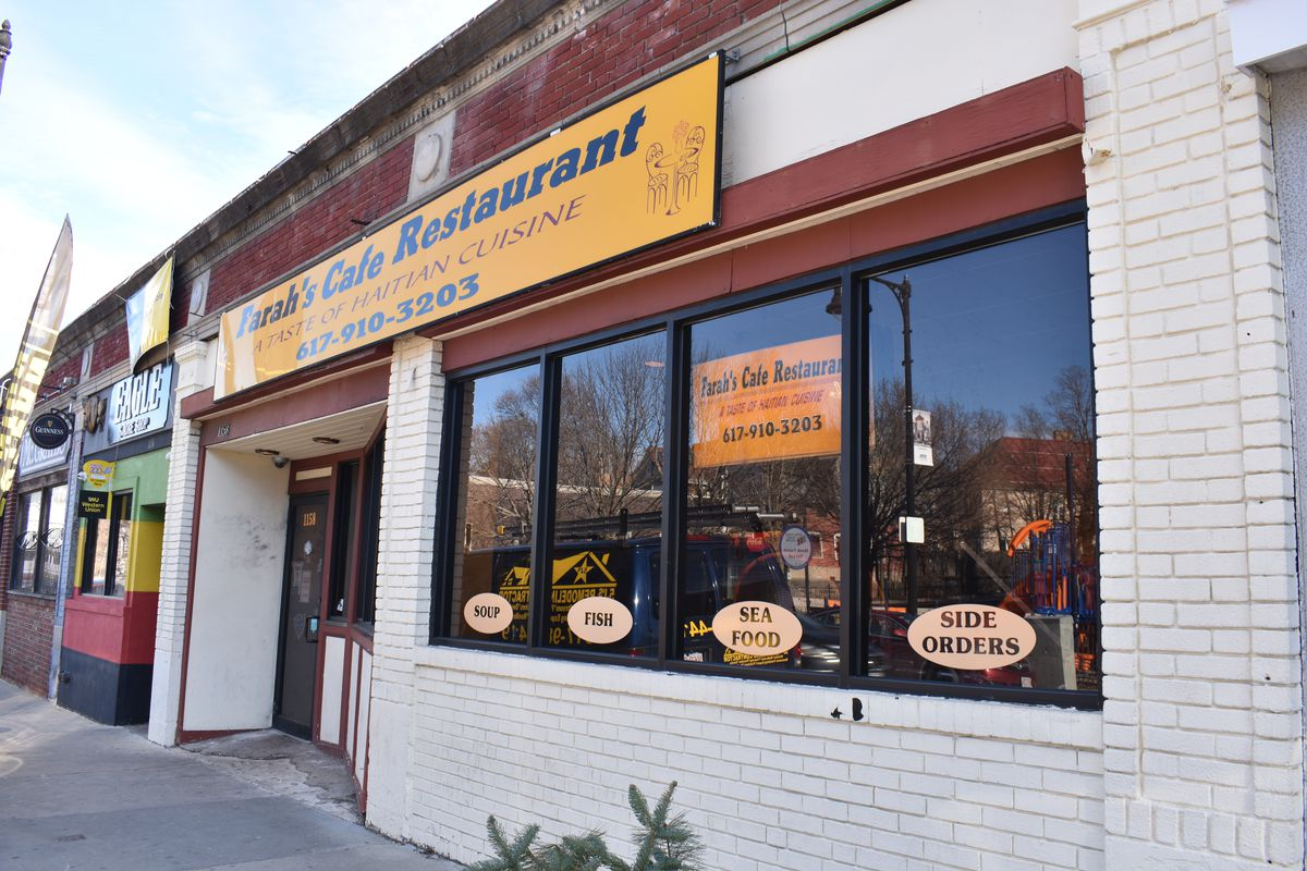 """A brick building, painted white, with a yellow and blue sign that reads """"Farah's Cafe Restaurant."""""""