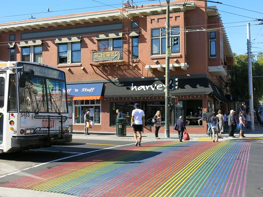 A street in San Francisco in the Castro neighborhood. The street has a rainbow painted on the crosswalk.