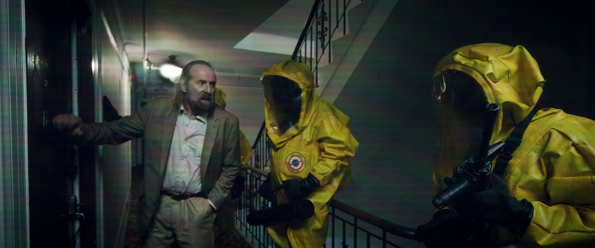 Peter Stormare points two people in yellow HAZMAT suits at an apartment door in Songbird